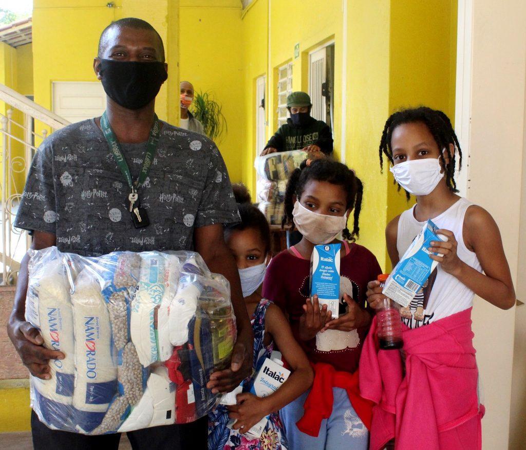 Imagem de uma família formada pelo pai e três meninas, todos com máscara e segurando itens de cesta básica.