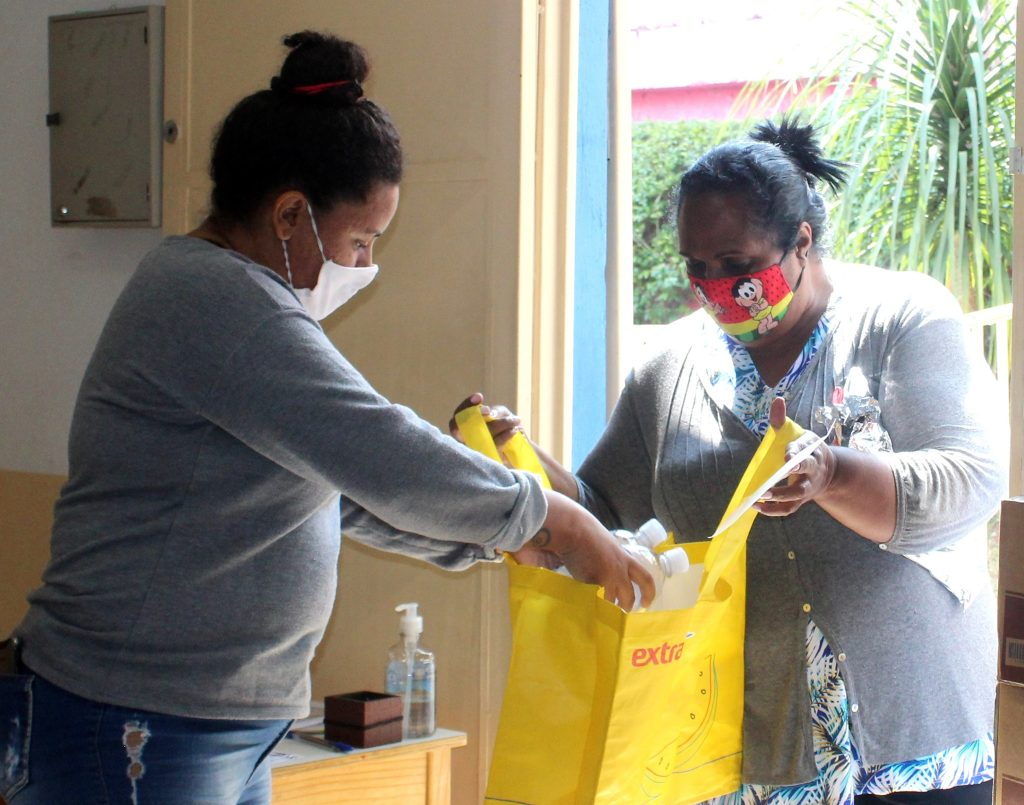 Imagem de colaboradora do Estrela Nova colocando kit de higiene em uma sacola de feira de uma moradora da comunidade que está a sua frente.