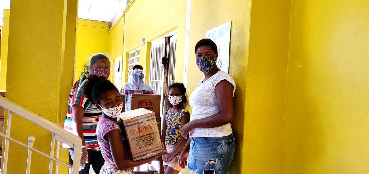 Imagem de uma família composta por duas mulheres e duas crianças, na sede do Estrela Nova recebendo sua cesta básica