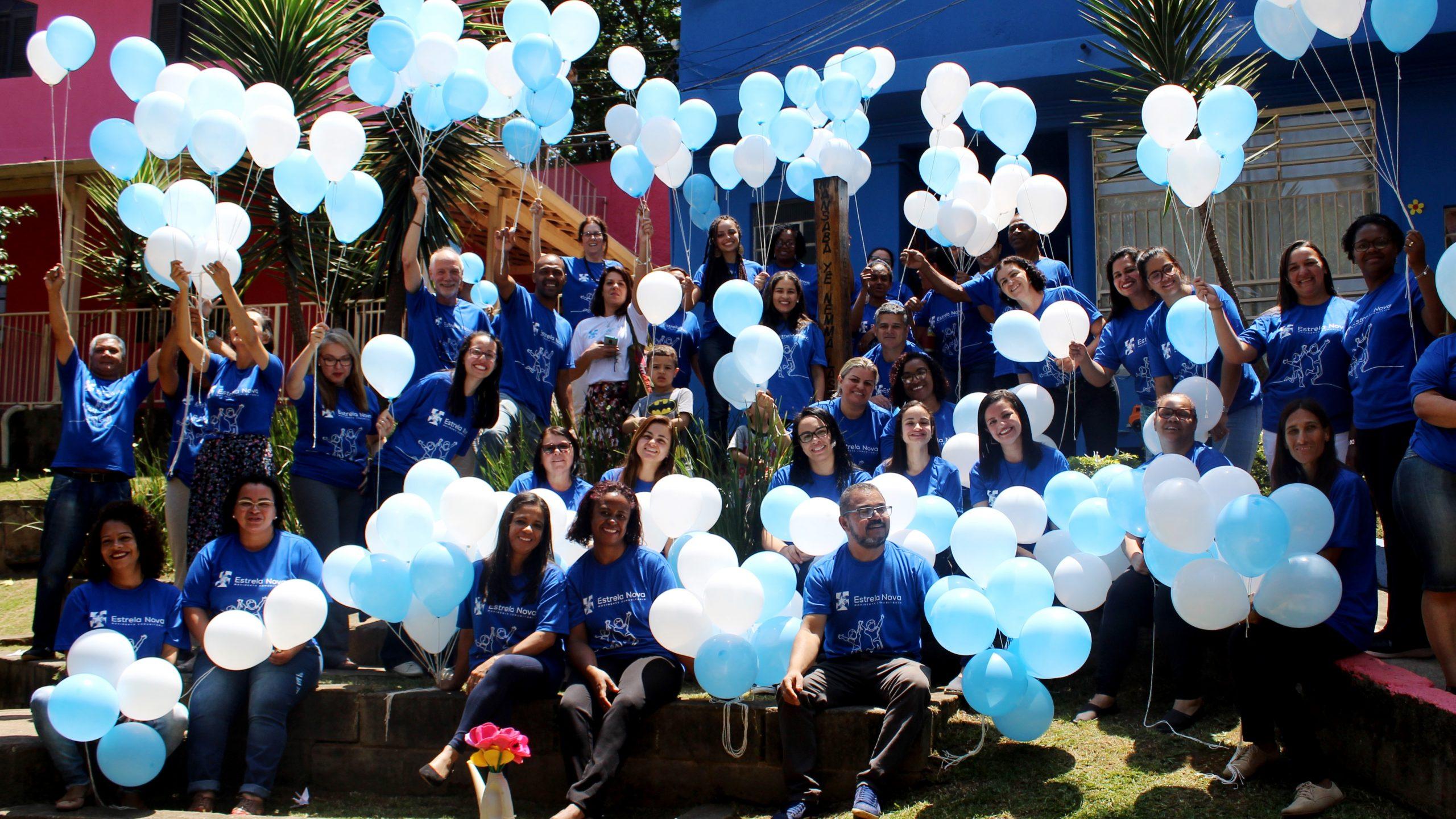 Imagem de colaboradores do Estrela Nova reunidos, todos com camiseta azul e segurando bexigas nas cores azul e branca.